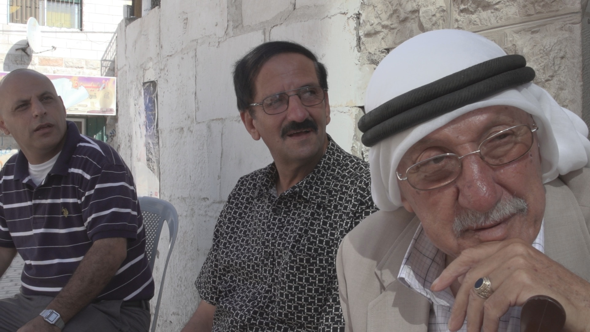 Three Arab men in front of cafe Al Birra West Bank